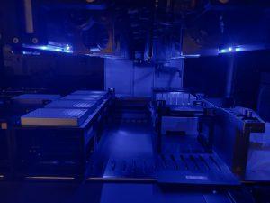 En titt in i roboten Hamilton. Pipettarm och hållare för provrör i blått sken. Foto.